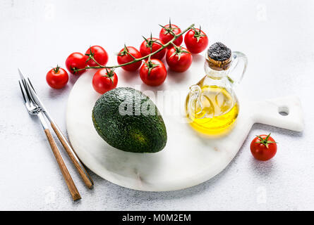 ingredients for guacamole on a marble board. Avocado and tomatoes with olive oil are ready to be used for a recipe - Stock Photo