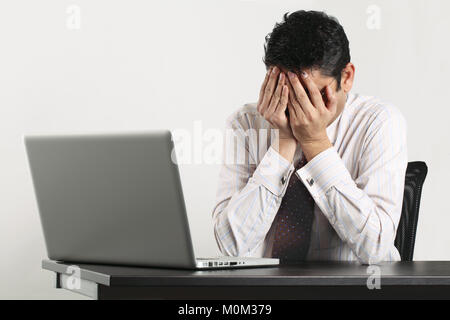 Photo of an Indian male frustrated with work sitting in front of a laptop. - Stock Photo