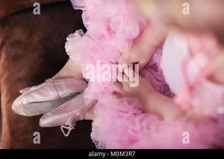 Overhead view of little girl in pink ballerina shoes and tutu - Stock Photo