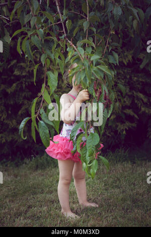 Little girl in swimsuit, hiding behind the low hanging branches of a tree - Stock Photo