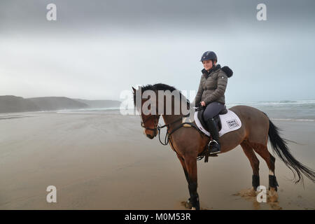 Horse rider riding away from the camera down the beach at low tide. Black & white image, with an obscured horizon - Stock Photo