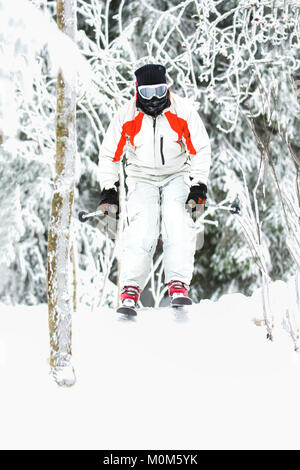 Freeride skier jumping on snowy slope in fir forest - Stock Photo