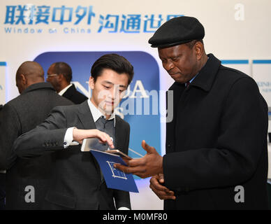(180123) -- BEIJING, Jan. 23, 2018 (Xinhua) -- A staff member shows the Xinhua News App to a foreign guest, in Beijing, - Stock Photo