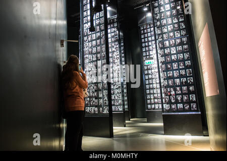 Gdansk, Poland. 23rd Jan, 2018. Visitors look at a mural with pictures of jewish victims in one of the exhibit rooms - Stock Photo