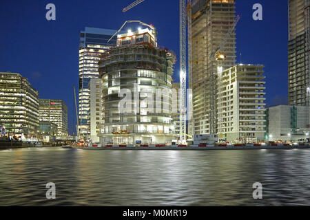 Dusk view of the construction of new residential towers in London's Canary Wharf district. Shows One Park Drive - Stock Photo