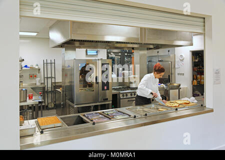 A catering assistant prepares school lunches in a new London primary school, UK. - Stock Photo