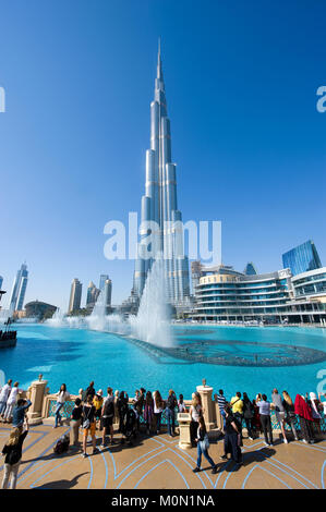 DUBAI, UNITED ARAB EMIRATES - JAN 02, 2018: Tourists are watching the fountainshow in front of the Burj Khalifa - Stock Photo