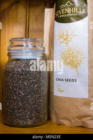 Chia seeds (salvia hispanica). Organic, uncooked, high in protein, vegan, superfood. In a packet and glass container - Stock Photo