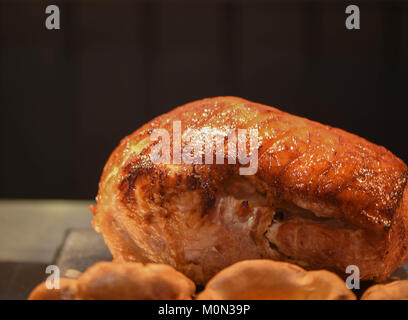 close up food photography image of a cooked and resting roast dinner joint of meat of a gammon or pork with a dark - Stock Photo