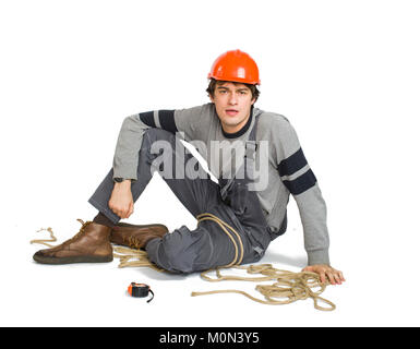 A young worker in grey uniform tied up with rope on white isolated background. - Stock Photo