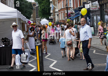 Crowd scene at the Marlyebone Summer Fayre Marlyebone Food Festival in London on a sunny day with yellow balloons and packed market stalls