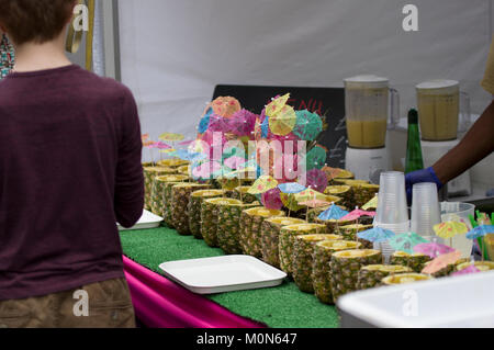 A row of fresh pineapples and colourful cocktail umbrellas at a street festival in Marlyebone London England on - Stock Photo