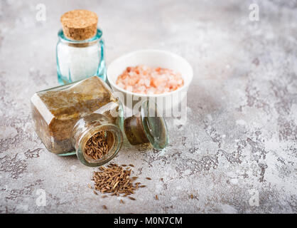 Cumin seeds in a glass bottle and sea salt on a light concrete background - Stock Photo
