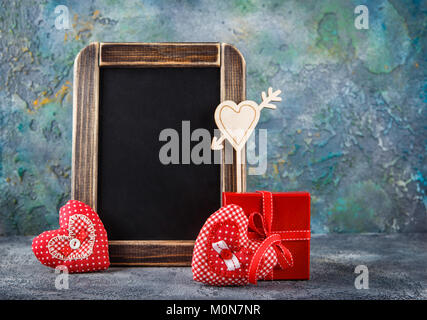 Two decorative textile handmade hearts, red gift box and chalkboard for Valentine's Day on blue concrete background - Stock Photo
