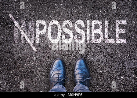 Changing the word impossible on possible on an asphalt road with feet - Stock Photo