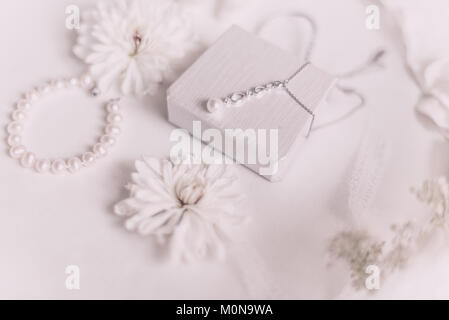 White bridal accessories for wedding background with pearls, white satin ribbons and lace, gloves, bracelet,flat - Stock Photo