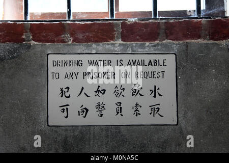 Indication Sign written on the wall in a prison or jail in english and chinese - Stock Photo