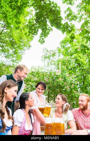 Waitress serving beer in beer garden - Stock Photo