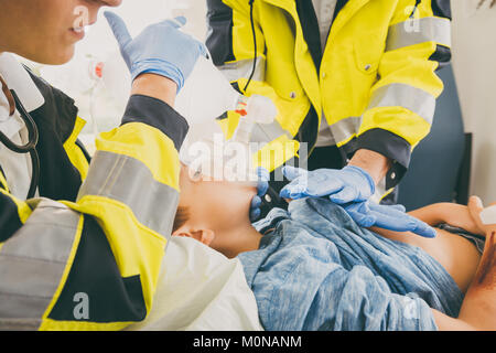 Emergency doctor giving cardiac massage for reanimation in ambul - Stock Photo