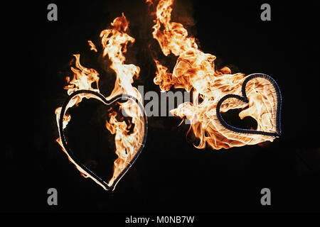 two hearts shaped firework on black background, fire show in night. happy valentine's day card. bengal fire burning heart. space for text. wedding or
