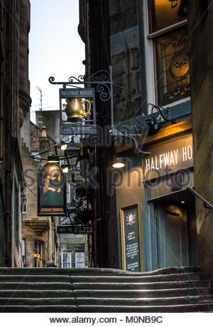Pub signs for Jinglin Geordie and Halfway House pubs in dark alley, Fleshmarket Close, Edinburgh, Scotland, UK - Stock Photo