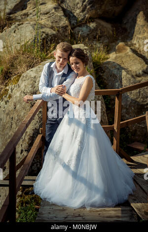 Full-length wedding shot of the charming young newlywed couple standing arm in arm and holding hands at the background - Stock Photo