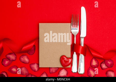 Valentines day restaurant. Knife and fork with a blank brown paper card - Stock Photo