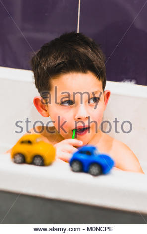 Toddler boy brushing his teeth in a bathtub on circa January 2018 in Poznan, Poland - Stock Photo