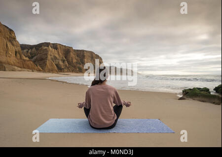 woman sitting on the beach on a yoga mat in the sitting lotus position, meditating. - Stock Photo