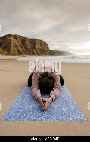 woman practicing yoga doing a child's pose at the beach - Stock Photo