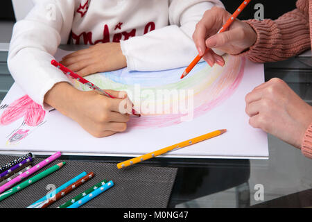 Mother and little daughter drawing a rainbow, partial view - Stock Photo