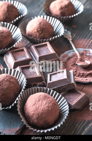 Rum balls with cocoa powder and chocolate slices on the wooden board - Stock Photo
