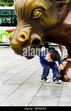 Shanghai, China. A young child investigates the bull statue in the Financial District on the Bund in Shanghai, China. - Stock Photo