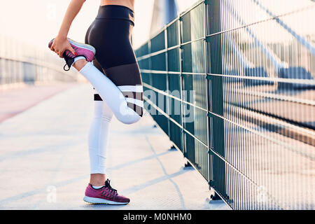 Close-up of woman stretching legs after running - Stock Photo