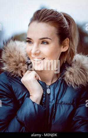 Portrait of smiling woman wearing winter jacket with fur collar - Stock Photo