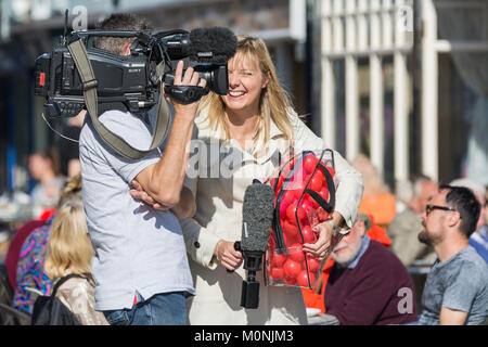 Female TV presenter laughing and smiling on the job, on an outside broadcast in the UK. - Stock Photo