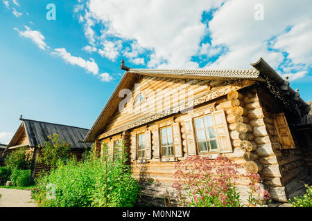 Wooden hut Slavic type on a summer day against the blue bright sky with clouds - Stock Photo