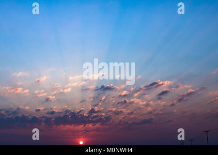 The sunset light pierces through the clouds causing innumerous rays of light.