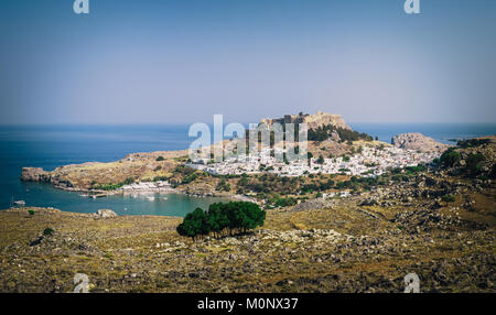Panoramic view on Lindos town with a beautiful lagoon and ancient fortress on a hill at Rhodes island, Greece - Stock Photo