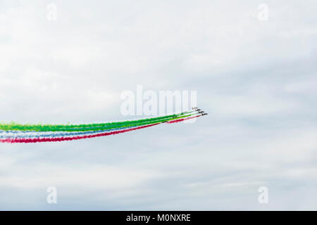 Airplanes on airshow with colorful bright trails of smoke against a blue sky, clouds. Aircraft, flying display and - Stock Photo
