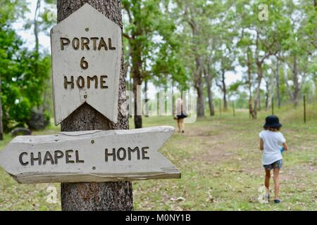 Women and child walking past a sign directing them to a chapel, Herveys Range Heritage Tea Rooms, Queensland, Australia - Stock Photo