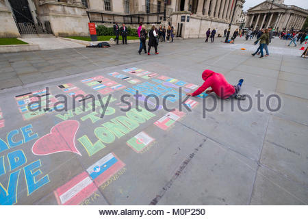 Man using colored chalk to draw flags of various countries on ground of Trafalgar Square, City of Westminster, London, - Stock Photo
