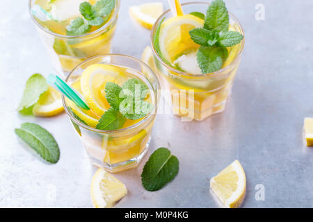 Iced lemon sweet tea with mint in chilled glasses on light grey table, delicious refreshment summer beverage - Stock Photo