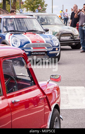 Red Austin mini with new BMW minis in the background, Union Jack paint. - Stock Photo