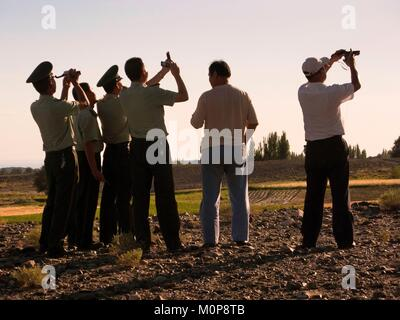 China,Xinjiang,Kumul Region,Chinese soldiers and inhabitants in a village observing the full solar eclipse - Stock Photo