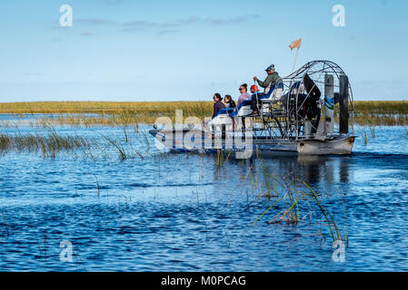 Tourists on air boat in the Florida Everglades at Sawgrass Recreation Park, airboat captain driving small group - Stock Photo