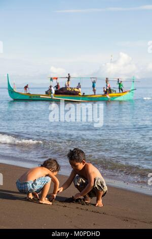 Philippines,Luzon,Albay Province,Tiwi,Sogod beach,children playing on the sand with a ringnet fishing boat coming - Stock Photo