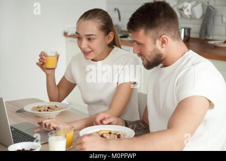 Young couple enjoying breakfast talking using laptop on dining t - Stock Photo