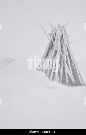 Wooden poles used for marking mountain trails in winter - Stock Photo