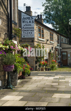 Small corner of Baildon town, with quaint stone, sunlit cottages, colourful flowers in planters & ghost sign on - Stock Photo